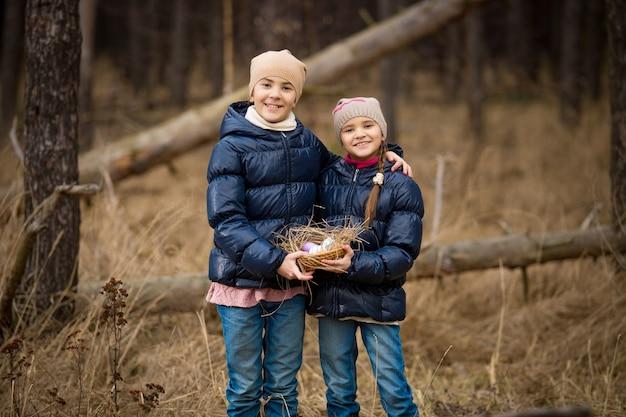 Duas meninas felizes segurando uma cesta cheia de ovos de páscoa