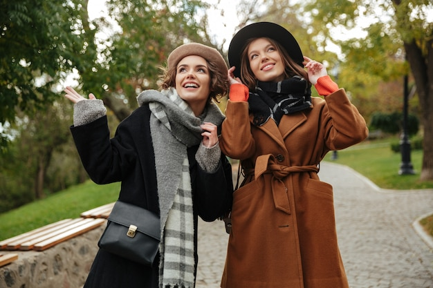 Duas meninas felizes, vestidas com roupas de outono andando