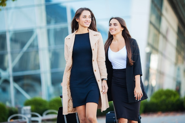 Duas meninas felizes viajando juntas para o exterior, carregando malas de bagagem no aeroporto
