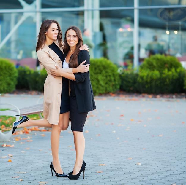Duas meninas felizes viajando juntos para o exterior, carregando bagagem mala no aeroporto