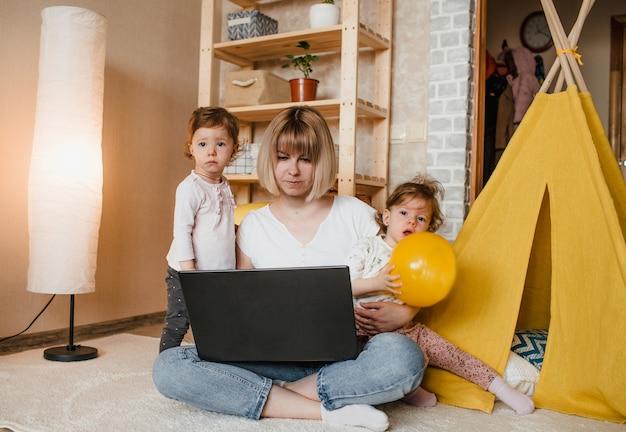 Duas meninas gêmeas impedem a mãe de trabalhar em casa no computador.