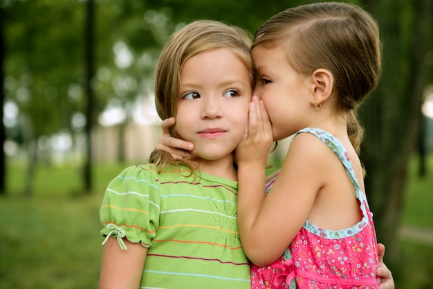 Duas meninas gêmeas irmãzinha sussurro no ouvido