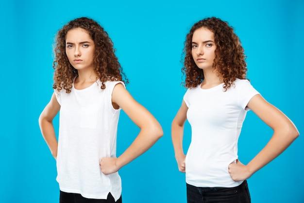 Duas meninas gêmeas posando com os braços akimbo sobre parede azul