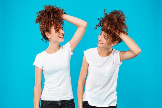 Duas meninas gêmeas segurando o cabelo, brincando sobre parede azul