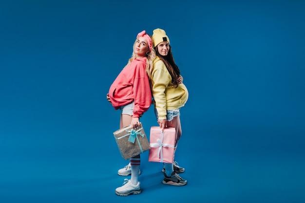 Duas meninas grávidas com presentes nas mãos, sobre um fundo azul isolado.