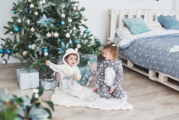 Duas meninas irmã abrem seus presentes na árvore de natal pela manhã