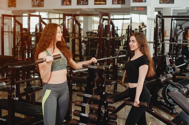 Duas meninas jovens e atléticas estão engajadas em esportes no ginásio