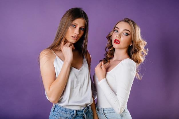 Duas meninas jovens e bonitas mostra emoções e sorrisos em um espaço roxo.