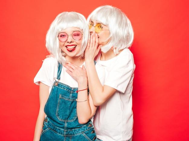 Duas meninas jovens hippie sexy em perucas brancas e lábios vermelhos. mulheres bonitas na moda em roupas de verão. modelos despreocupados posando perto de parede vermelha no verão de estúdio compartilham segredo, fofoca