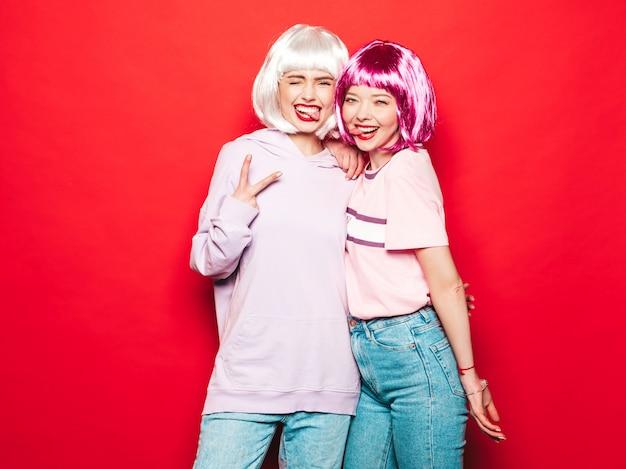 Duas meninas jovens hippie sexy em perucas e lábios vermelhos. belas mulheres na moda em roupas de verão. modelos despreocupados posando perto de parede vermelha no estúdio enlouquecendo. mostra a língua