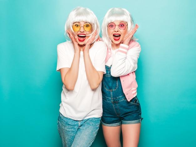 Duas meninas jovens hipster sexy de perucas brancas e lábios vermelhos. belas mulheres chocadas e surpresas em roupas de verão. modelos despreocupados posando perto de parede azul no verão de estúdio enlouquecendo