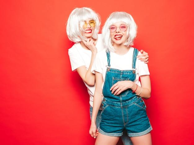 Duas meninas jovens hipster sexy em perucas brancas e lábios vermelhos. mulheres bonitas na moda em roupas de verão. modelos despreocupados posando perto de parede vermelha no verão de estúdio em óculos de sol