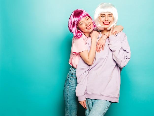 Duas meninas jovens hipster sexy em perucas e lábios vermelhos. belas mulheres na moda em roupas de verão. modelos despreocupados posando perto da parede azul no estúdio enlouquecendo. mostra a língua