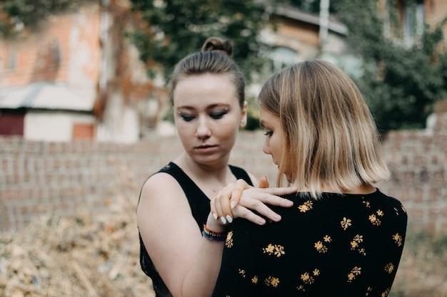 Duas meninas jovens lésbicas abraçando ao ar livre.