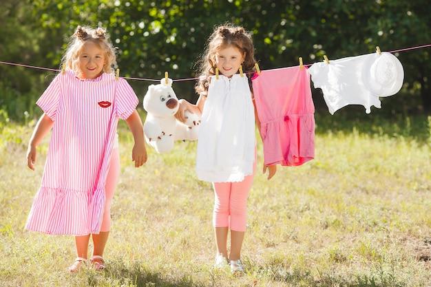 Duas meninas lavando roupa. irmãs fazendo trabalhos domésticos