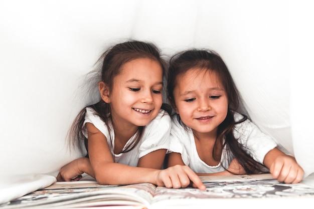 Duas meninas lendo embaixo do cobertor