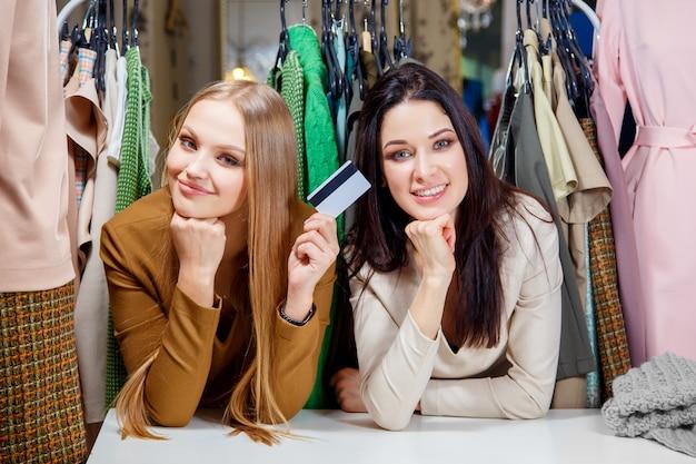 Duas meninas lindas fazer compras com cartão de crédito e sorrindo em uma loja de roupas