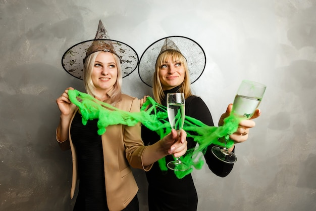 Duas meninas lindas vestindo vestido preto bruxa fazendo festa