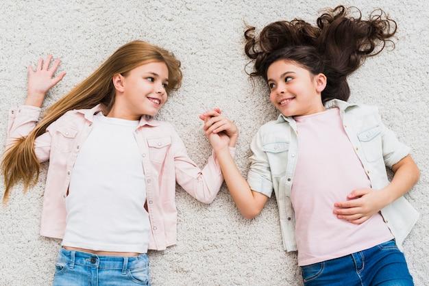 Duas meninas, mentindo, branco, tapete, segurando mão, olhando um ao outro