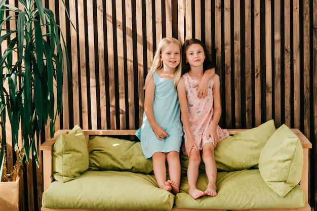 Duas meninas modelo em lindos vestidos, sentado na cama de limão com parede de madeira