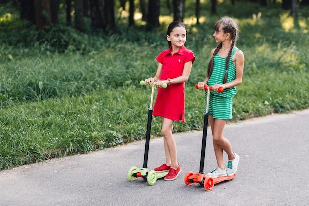 Duas meninas, montando, pontapé scooter, em, rua