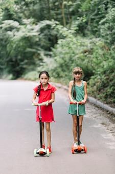 Duas meninas, montando, scooters, ligado, estrada