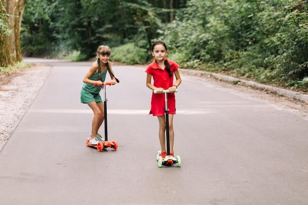 Duas meninas, montando, scooters, ligado, rua reta