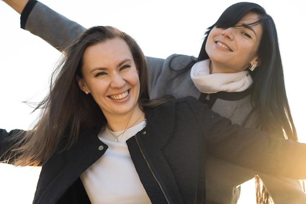 Duas meninas morenas brancas felizes no parque ensolarado de outono. amigos brincalhões.