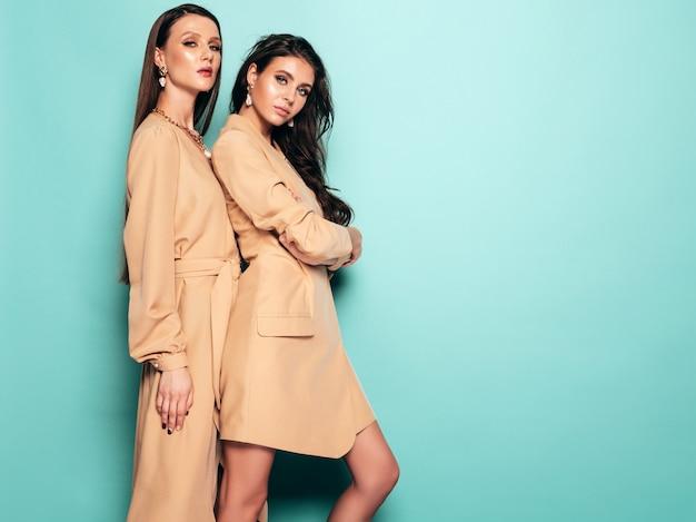 Duas meninas morenas lindas em roupas de verão na moda agradável. mulheres despreocupadas sexy posando perto da parede azul no estúdio
