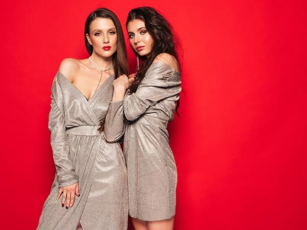 Duas meninas morenas lindas em vestido brilhante verão na moda agradável