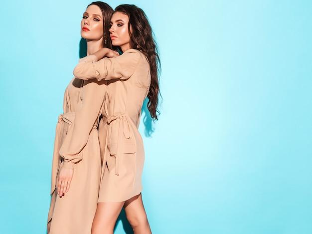Duas meninas morenas lindas jovens em roupas de verão na moda agradável. mulheres despreocupadas sexy posando perto da parede azul no estúdio.