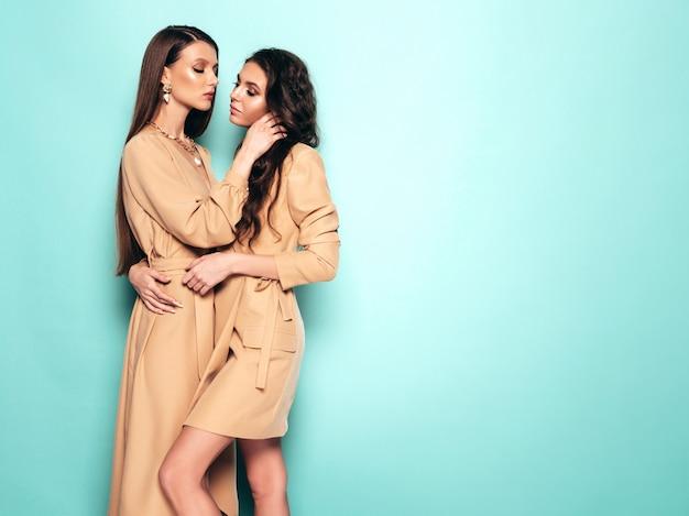 Duas meninas morenas lindas jovens no verão na moda agradável semelhante ternos roupas. mulheres despreocupadas sexy posando perto da parede azul no estúdio
