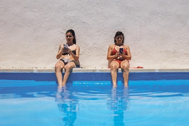 Duas meninas morenas sentadas na beira da piscina enquanto tomam sol
