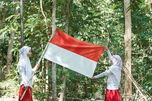 Duas meninas muçulmanas com lenço na cabeça segurando uma bandeira vermelha e branca