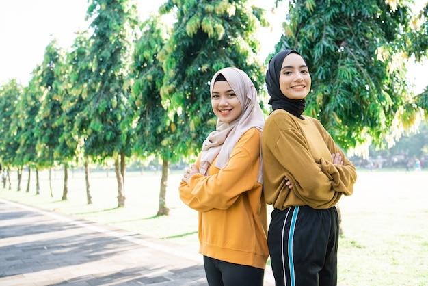 Duas meninas muçulmanas ficam de costas um para o outro com as mãos cruzadas enquanto se exercitam no parque