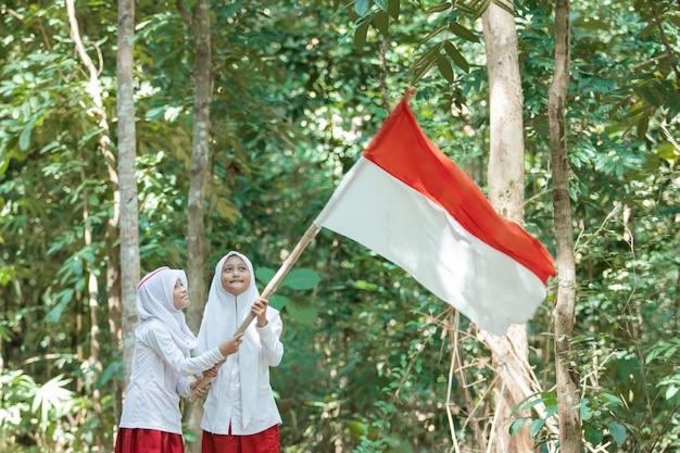 Duas meninas muçulmanas usando véus segurando uma grande bandeira vermelha e branca e hasteando a bandeira