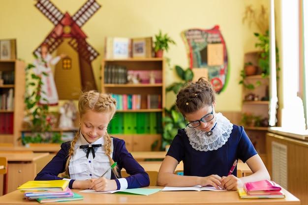Duas meninas na turma da escola escrevem em um caderno