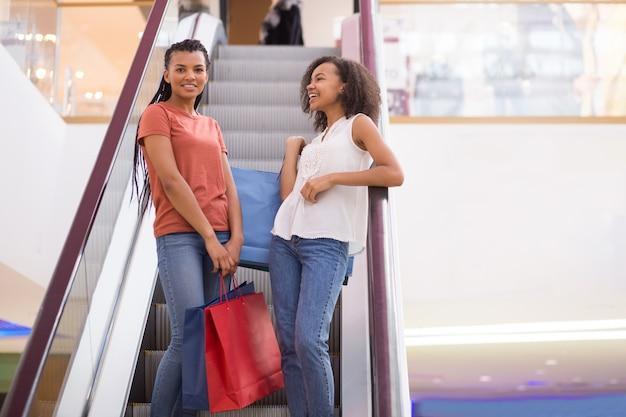 Duas meninas negras sorrindo conversando na escada rolante no shopping