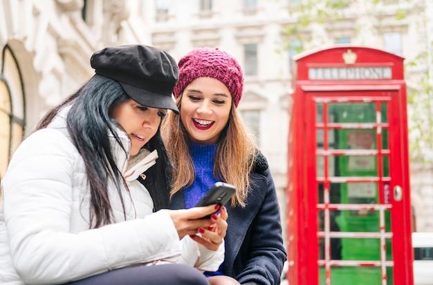 Duas meninas olham para o telefone móvel em uma rua de londres com uma cabine telefônica vermelha ao fundo.