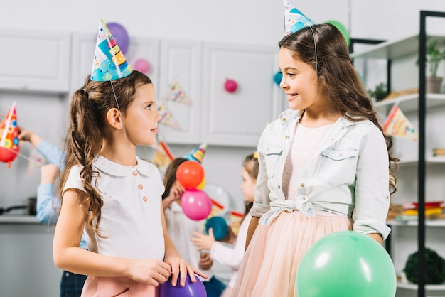 Duas meninas, olhando um ao outro, enquanto, celebrando, aniversário, em, cozinha