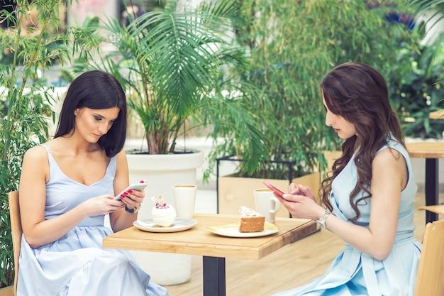 Duas meninas parece smartphone no café ao ar livre no fundo da natureza.