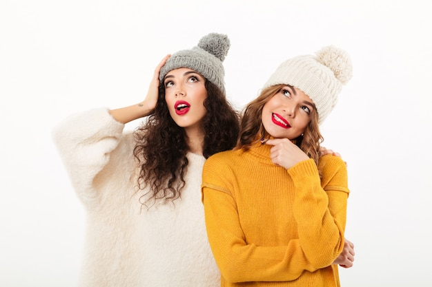 Duas meninas pensativas em blusas e chapéus posando juntos enquanto olha para cima sobre parede branca