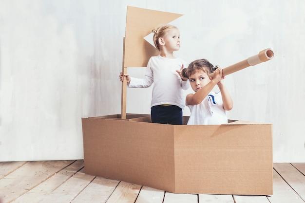Duas meninas pequenas em casa em um navio de papelão brincam de capitães e marinheiros