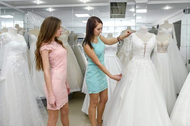 Duas meninas perto de um manequim na loja de casamentos