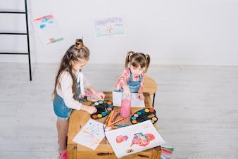 Duas meninas pintando com aquarelle na mesa de madeira