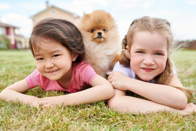 Duas meninas posando com cachorro ao ar livre