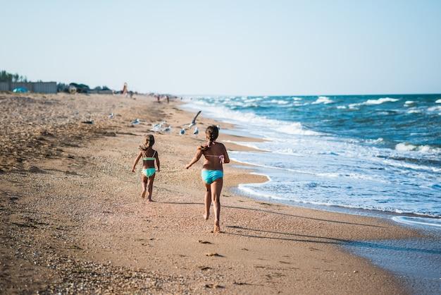 Duas meninas positivas correndo ao longo da praia em um dia quente e ensolarado de verão