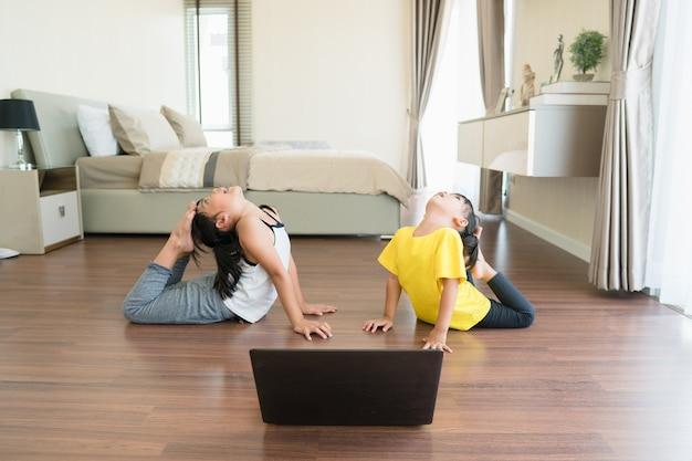 Duas meninas praticando ioga, alongamento, fitness por vídeo no notebook.