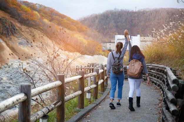 Duas meninas que andam na rua e árvore de bordo amarela vermelha na estação do outono, tomada de japão.