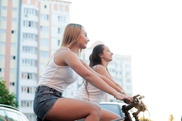 Duas meninas que têm uma noite perfeita em suas bicicletas